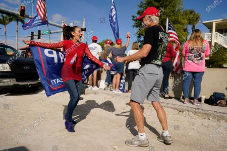 Supporters of President Donald Trump, Jennifer Aiello, left, Ron Raven dance as they wait for the motorcade on the road to Mar-a-Lago, Trump's Palm Beach estate,, in West Palm Beach, Fla