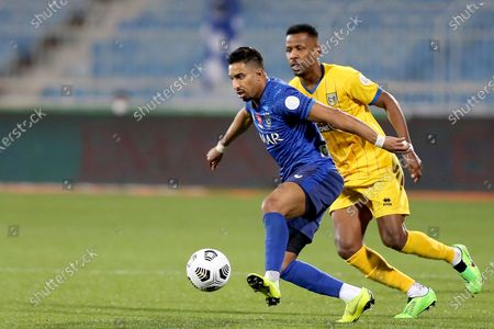 Al-Hilal's player Salem Al-Dawsari (L) in action against Al-Taawoun's Mohammed Abusabaan (R) during the Saudi Professional League soccer match between Al-Hilal and Al-Taawoun at Prince Faisal bin Fahd Stadium, Riyadh, Saudi Arabia, 20 January 2021.
