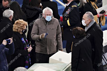 Senate Minority Leader Chuck Schumer, a Democrat from New York, from right, Senator Bernie Sanders, an Independent from Vermont, and Senator Debbie Stabenow, a Democrat from Michigan, wear protective masks during the 59th presidential inauguration in Washington, D.C., U.S.,. Biden will propose a broad immigration overhaul on his first day as president, including a shortened pathway to U.S. citizenship for undocumented migrants - a complete reversal from Donald Trump's immigration restrictions and crackdowns, but one that faces major roadblocks in Congress. Photographer: Kevin Dietsch/UPI