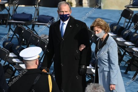 Former US President George W Bush (L) and Laura Bush are seen before US president-elect Joe Biden is sworn in as the 46th US President, at the US Capitol in Washington, DC. - Biden, a 78-year-old former vice president and longtime senator, takes the oath of office at noon (1700 GMT) on the US Capitol's western front, the very spot where pro-Trump rioters clashed with police two weeks ago before storming Congress in a deadly insurrection.