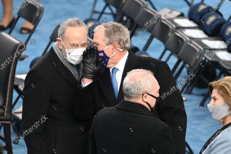 Stock Image of Former US President George W Bush (R) talks with Senate Majority leader Chuck Schumer before US president-elect Joe Biden is sworn in as the 46th US President, at the US Capitol in Washington, DC. - Biden, a 78-year-old former vice president and longtime senator, takes the oath of office at noon (1700 GMT) on the US Capitol's western front, the very spot where pro-Trump rioters clashed with police two weeks ago before storming Congress in a deadly insurrection.