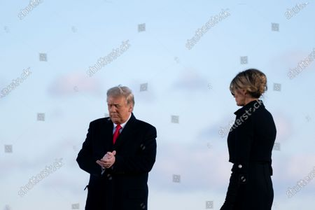 U.S. President Donald Trump, left, and U.S. First Lady Melania Trump prepare to depart a farewell ceremony at Joint Base Andrews, Maryland, U.S.,. Trump departs Washington with Americans more politically divided and more likely to be out of work than when he arrived, while awaiting trial for his second impeachment - an ignominious end to one of the most turbulent presidencies in American history. Photographer: Stefani Reynolds/Bloomberg