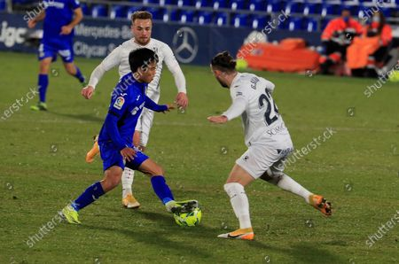 Getafe's midfielder Take Kubo (2-L) vies for the ball with Huesca's midfielder Javi Ontiveros (L) and defender Gaston Silva (R) during the Spanish LaLiga soccer match between Getafe CF and Huesca SD held at Coliseum Alfonso Perez stadium, in Getafe, Madrid, central Spain, 20 January 2021.