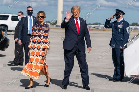 President Donald Trump with first lady Melania Trump waves upon arrival at Palm Beach International Airport in West Palm Beach, Fla