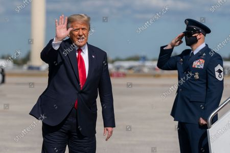 Former President Donald Trump waves to the members of the media after his final flight on Air Force One at Palm Beach International Airport in West Palm Beach, Fla