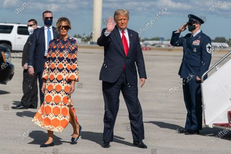 Former President Donald Trump and Melania Trump waves upon arrival from their final flight on Air Force One at Palm Beach International Airport in West Palm Beach, Fla