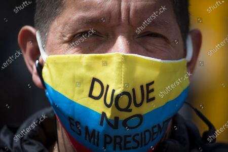 "Protester wears a mask with the Colombian flag colors and Spanish message ""Duque isn't my president,"" referring to President Ivan Duque, during the march toward the residence of Bogota Mayor Claudia Lopez to demand the lifting of the city-wide curfew and the reopening of business amid the COVID-19 pandemic in Bogota, Colombia"