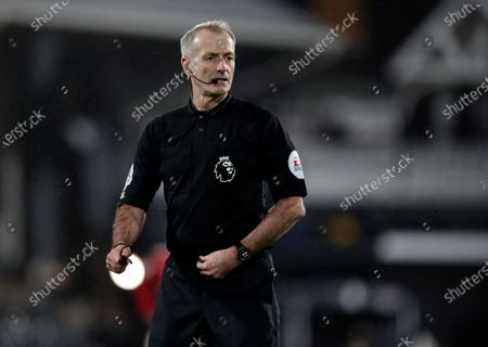 Referee Martin Atkinson looks out during the English Premier League soccer match between Fulham and Manchester United at the Craven Cottage stadium in London