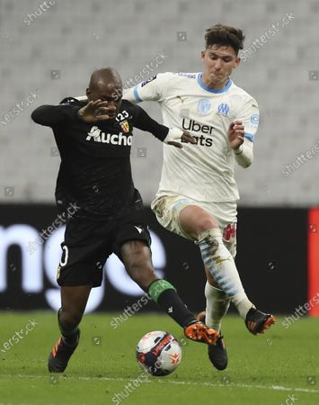 Marseille's Leonardo Balerdi, right, tries to stop Lens' Gael Kakuta during the French League One soccer match between Marseille and Lens at the Veledrome stadium in Marseille, France