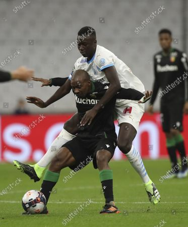 Marseille's Pape Gueye, background, stops Lens' Gael Kakuta during the French League One soccer match between Marseille and Lens at the Veledrome stadium in Marseille, France