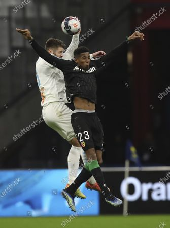 Marseille's Duje Caleta-Car, background, and Lens' Simon Banza jump for the ball during the French League One soccer match between Marseille and Lens at the Veledrome stadium in Marseille, France