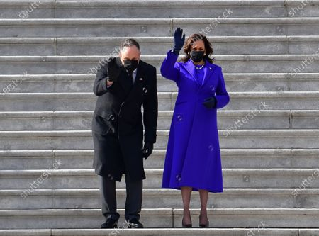 Vice President Kamala Harris and husband Douglas Emhoff wave on the east side steps of the U.S. Capitol as former Vice President Mike Pence and wife Karen Pence depart after the Presidential Inauguration in Washington on