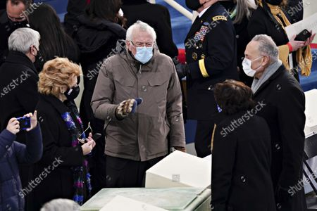 Senate Minority Leader Chuck Schumer, a Democrat from New York, from right, Senator Bernie Sanders, an Independent from Vermont, and Senator Debbie Stabenow, a Democrat from Michigan, wear protective masks during the 59th presidential inauguration in Washington, D.C., U.S., on Wednesday, Jan. 20, 2021. Biden will propose a broad immigration overhaul on his first day as president, including a shortened pathway to U.S. citizenship for undocumented migrants - a complete reversal from Donald Trump's immigration restrictions and crackdowns, but one that faces major roadblocks in Congress.