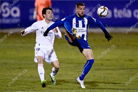 Real Madrid's Alvaro Odriozola, left challenges for the ball with Alcoyano's Ramon during a Spanish Copa del Rey round of 32 soccer match between Alcoyano and Real Madrid at the El Collao stadium in Alcoy, Spain