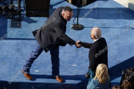 Country singer Garth Brooks reaches out to greet President Joe Biden during the 59th Presidential Inauguration at the U.S. Capitol in Washington, DC