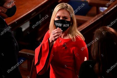 "Rep. Marjorie Taylor Greene, R-Ga., wears a ""Trump Won"" face mask as she arrives on the floor of the House to take her oath of office on opening day of the 117th Congress at the U.S. Capitol in Washington. President Joe Biden's inauguration has sown a mixture of anger, confusion and disappointment among believers in the baseless QAnon conspiracy theory. Greene, who has expressed support for the conspiracy theories, called for Biden's impeachment across her Twitter, Facebook and Telegram accounts as the new president was sworn in, Wednesday, Jan. 20"