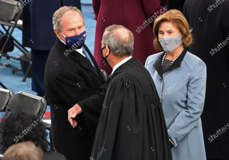 Stock Photo of Former President George W. Bush and his wife Laura Bush greet Chief Justice John Roberts as they arrive to witness President Joseph Robinette Biden Jr. take the oath of office as the 46th President of the United States