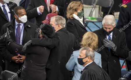 Former President George W. Bush takes a selfie as wife Laura Bush talks with former President Bill Clinton as they arrive for the Inauguration of President Biden at the U.S. Capitol in Washington, DC on Wednesday, January 20, 2021