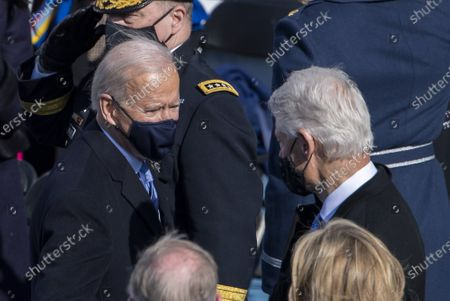 President Joe Biden greets former President Bill Clinton as he departs after the Inauguration Ceremony at the U.S. Capitol in Washington, DC on Wednesday, January 20, 2021. Bottom right is former President George W. Bush.