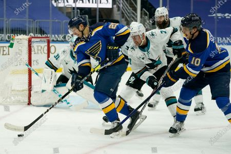 St. Louis Blues' Jordan Kyrou (25) controls the puck as teammate Brayden Schenn (10) and San Jose Sharks' Dylan Gambrell (7) watch during the second period of an NHL hockey game, in St. Louis