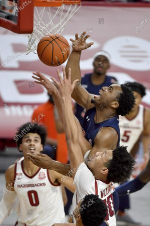 Auburn forward Chris Moore tries to shoot over Arkansas defenders Jaylin Williams (10) and Justin Smith (0) during the second half of an NCAA college basketball game, in Fayetteville, Ark