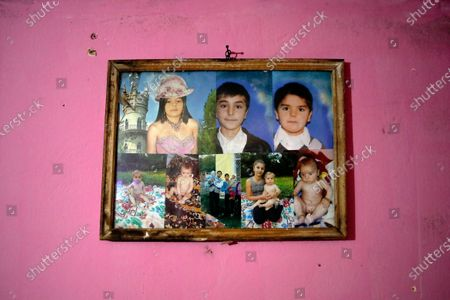 A frame with several pictures of children assisted by Valeriu Nicola, hangs on a wall in their family home in Nucsoara, Romania, . A gentle hero to many in Romania, Valeriu Nicolae says that, at heart, he is more like former NBA star Michael Jordan - highly competitive and eager to improve in what he does best. In Nicolae's case that is helping others. The rights activist has earned praise for his tireless campaign to change for the better the lives of the Balkan country's poorest and underprivileged residents, particularly the children