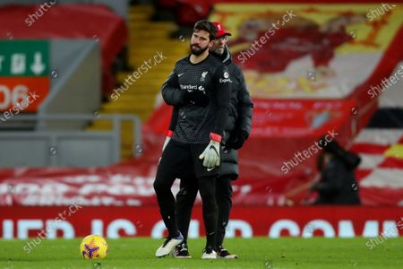 Liverpool Manager Jurgen Klopp pulls goalkeeper Alisson Becker away from the referee at the end of the match