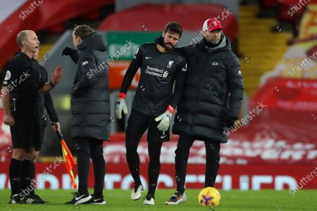 Liverpool Manager Jurgen Klopp pulls goalkeeper Alisson Becker away from referee Mike Dean at the end of the match