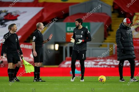 Stock Photo of Liverpool goalkeeper Alisson Becker speaks with referee Mike Dean at the end of the match