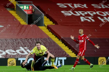 Ashley Barnes of Burnley goes down in the area under the challenge by Liverpool goalkeeper Alisson Becker
