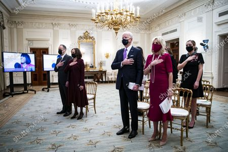 U.S. President Joe Biden, U.S. First Lady Dr. Jill Biden, U.S. Vice President Kamala Harris, and her husband Doug Emhoff, place their hands over their hearts as Patti LaBelle sings the National Anthem, during a virtual presidential inaugural prayer service in the State Dining Room of the White House in Washington, D.C., USA, 21 January 2021. Biden in his first full day in office plans to issue a sweeping set of executive orders to tackle the raging Covid-19 pandemic that will rapidly reverse or refashion many of his predecessor's most heavily criticized policies.