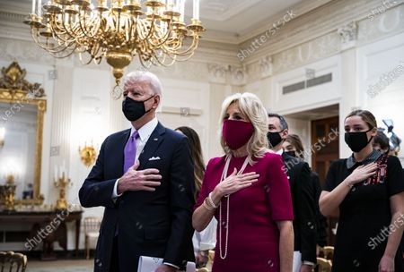 US President Joe Biden and US First Lady Dr. Jill Biden, place their hands over their hearts as Patti LaBelle sings the National Anthem, during a virtual presidential inaugural prayer service in the State Dining Room of the White House in Washington , DC, USA, 21 January 2021. Biden in his first full day in office plans to issue a sweeping set of executive orders to tackle the raging Covid-19 pandemic to rapidly reverse or refashion many of his predecessor's most heavily criticized policies.
