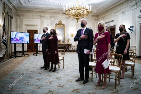US President Joe Biden (C), US First Lady Dr. Jill Biden (2-R), US Vice President Kamala Harris (2-L), and her husband Doug Emhoff (L), place their hands over their hearts as Patti LaBelle sings the National Anthem, during a virtual presidential inaugural prayer service in the State Dining Room of the White House in Washington, DC, USA, 21 January 2021. Biden in his first full day in office plans to issue a sweeping set of executive orders to tackle the raging Covid-19 pandemic to rapidly reverse or refashion many of his predecessor's most heavily criticized policies.