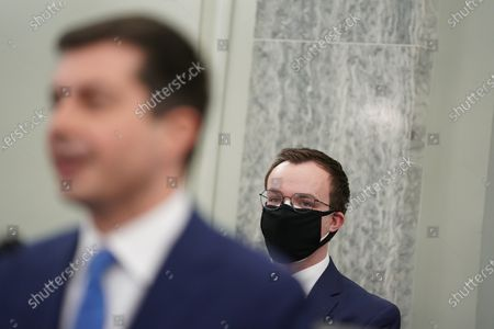 """Stock Image of Pete Buttigieg, U.S. secretary of transportation nominee for U.S. President Joe Biden, left, speaks as husband Chasten Buttigieg, right, wears a protective mask while listening during a Senate Commerce, Science and Transportation Committee confirmation hearing in Washington, D.C., U.S.,. Buttigieg, is pledging to carry out the administration's ambitious agenda to rebuild the nation's infrastructure, calling it a """"generational opportunity"""" to create new jobs, fight economic inequality and stem climate change. Credit: Stefani Reynolds / Pool via CNP"""