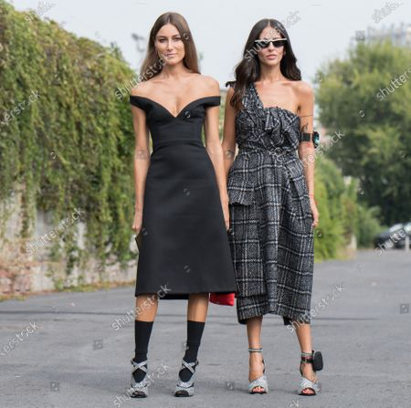 Giorgia Tordini (left) wears a black off shoulder dress, black socks and silver high heel sandals. Gilda Ambrosio wears a checkered dress, a Prada mini bag on the arm and silver high heels with embedded cristals outside the Prada show during Milan Fashion Week Womenswear Spring/Summer 2020, on September 18, 2020 in Milan, Italy.