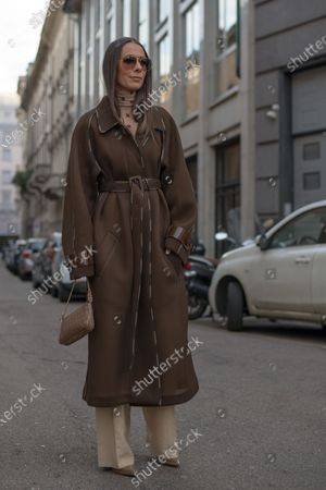 Alice Barbier wears sheer turtle neck top by Fendi, a brown coat by Fendi, bag by Fendi and beige troussers outside the Max Mara show during Milan Fashion Week Womenswear Autumn/Winter 2020/21, on February 20, 2020 in Milan, Italy.