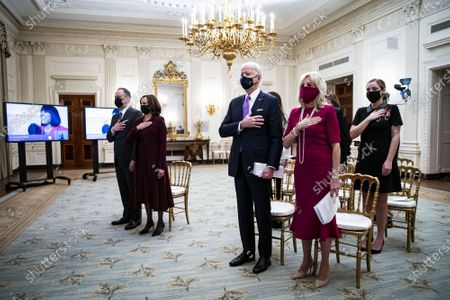 U.S. President Joe Biden, U.S. First Lady Dr. Jill Biden, U.S. Vice President Kamala Harris, and her husband Doug Emhoff, place their hands over their hearts as Patti LaBelle sings the National Anthem, during a virtual presidential inaugural prayer service in Biden's first day in office in the State Dining Room of the White House in Washington, DC on Thursday, January 21, 2021.