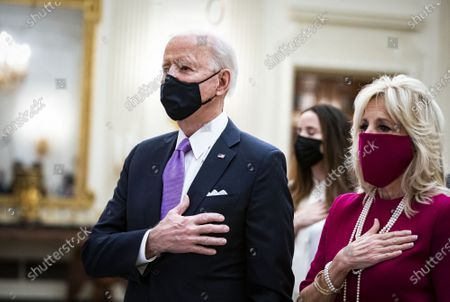 U.S. President Joe Biden and U.S. First Lady Dr. Jill Biden, place their hands over their hearts as Patti LaBelle sings the National Anthem, during a virtual presidential inaugural prayer service in the State Dining Room of the White House in Washington, DC on Thursday, January 21, 2021.