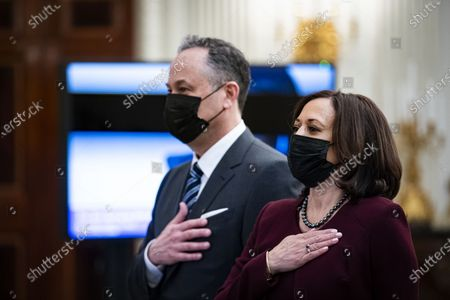 U.S. Vice President Kamala Harris and her husband Doug Emhoff, place their hands over their hearts as Patti LaBelle sings the National Anthem, during a virtual presidential inaugural prayer service in the State Dining Room of the White House in Washington, D.C., U.S.,. Biden in his first full day in office plans to issue a sweeping set of executive orders to tackle the raging Covid-19 pandemic that will rapidly reverse or refashion many of his predecessor's most heavily criticized policies.