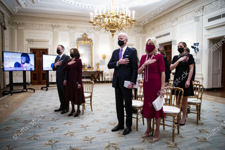 Stock Image of U.S. President Joe Biden, U.S. First Lady Dr. Jill Biden, U.S. Vice President Kamala Harris, and her husband Doug Emhoff, place their hands over their hearts as Patti LaBelle sings the National Anthem, during a virtual presidential inaugural prayer service in the State Dining Room of the White House in Washington, D.C., U.S.,. Biden in his first full day in office plans to issue a sweeping set of executive orders to tackle the raging Covid-19 pandemic that will rapidly reverse or refashion many of his predecessor's most heavily criticized policies.
