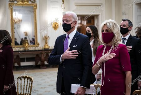 U.S. President Joe Biden and U.S. First Lady Dr. Jill Biden, place their hands over their hearts as Patti LaBelle sings the National Anthem, during a virtual presidential inaugural prayer service in the State Dining Room of the White House in Washington, D.C., U.S.,. Biden in his first full day in office plans to issue a sweeping set of executive orders to tackle the raging Covid-19 pandemic that will rapidly reverse or refashion many of his predecessor's most heavily criticized policies.