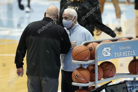 North Carolina head coach Roy Williams, right, greets Wake Forest head coach Steve Forbes prior to an NCAA college basketball game in Chapel Hill, N.C