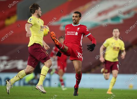 Liverpool's Joel Matip, center, tries to control the ball during the English Premier League soccer match between Liverpool and Burnley in Liverpool, England
