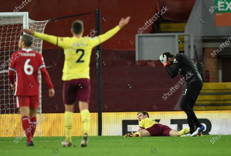 Liverpool's goalkeeper Alisson, right, reacts after giving out a penalty to Burnley's Ashley Barnes during the English Premier League soccer match between Liverpool and Burnley in Liverpool, England