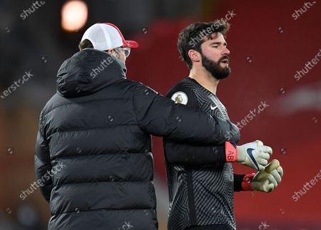 Liverpool's manager Jurgen Klopp, left pulls back his goalkeeper Alisson protesting to the match referee following the English Premier League soccer match between Liverpool and Burnley in Liverpool, England, . Burnley won the match 0-1