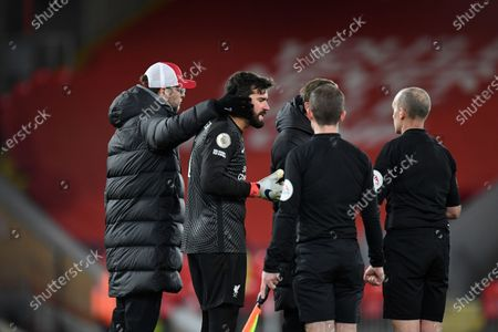 Liverpool's manager Jurgen Klopp, left and his goalkeeper Alisson center, protest to the match referee Mike Dean, right, following the English Premier League soccer match between Liverpool and Burnley in Liverpool, England, . Burnley won the match 0-1