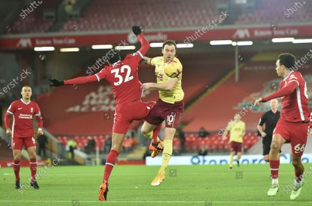Liverpool's Joel Matip, left, and Burnley's Ashley Barnes, right, jump for the ball during the English Premier League soccer match between Liverpool and Burnley in Liverpool, England