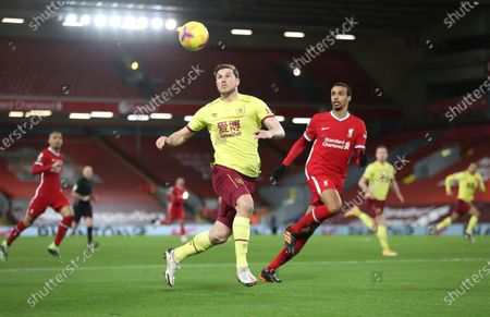 Burnley's Chris Wood, cetner, tries to control the ball as Liverpool's Joel Matip, right follows him, during the English Premier League soccer match between Liverpool and Burnley in Liverpool, England