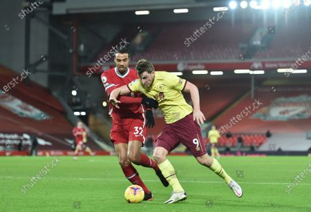 Burnley's Chris Wood, right, tries to dribble past Liverpool's Joel Matip during the English Premier League soccer match between Liverpool and Burnley in Liverpool, England