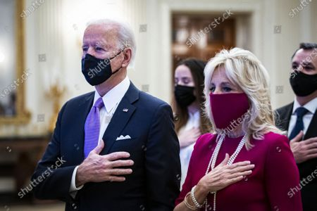 Stock Photo of U.S. President Joe Biden and U.S. First Lady Dr. Jill Biden, place their hands over their hearts as Patti LaBelle sings the National Anthem, during a virtual presidential inaugural prayer service in the State Dining Room of the White House in Washington, DC on Thursday, January 21, 2021.